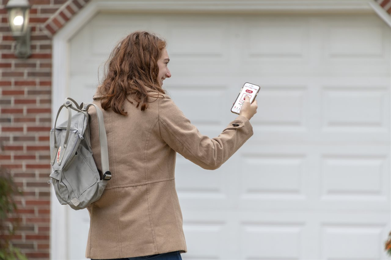 a woman looking at her phone outside the garage | ALLIN Home Inspections | Connectivity Sterling