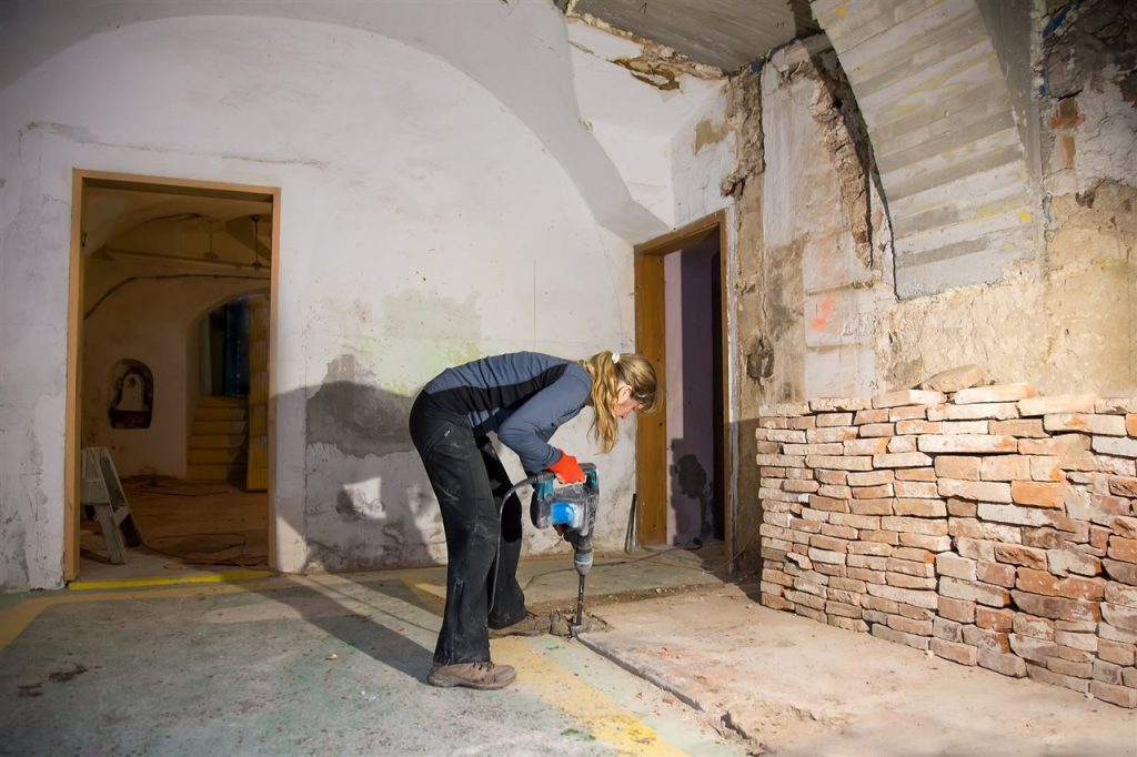 woman drilling the basement floor | ALLIN Home Inspections, Inc. | Bathroom in the basement Sterling